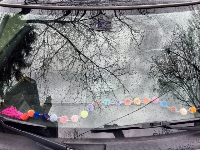 Pompoms on a dashboard.
